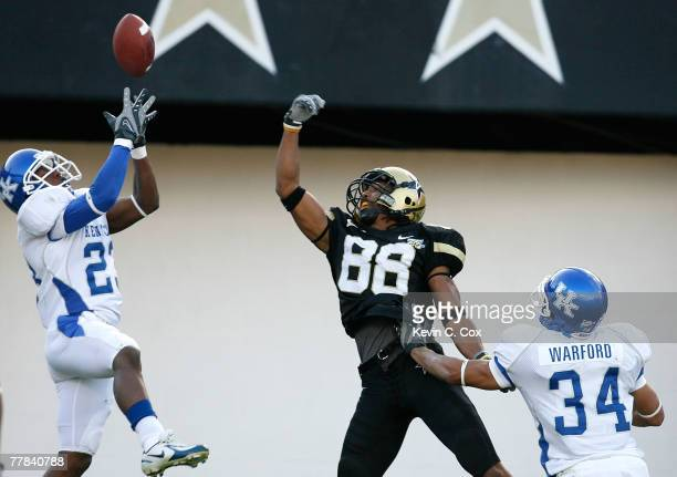 Cornerback Paul Warford defends as Shomari Moore of the Kentucky Wildcats nearly picks off a pass intended for receiver George Smith of the...