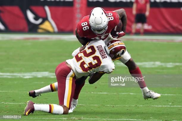 Cornerback Quinton Dunbar of the Washington Redskins tackles tight end Ricky SealsJones of the Arizona Cardinals during the third quarter at State...