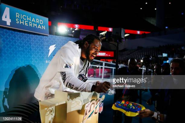 Cornerback Richard Sherman of the San Francisco 49ers speaks to the media during Super Bowl Opening Night presented by BOLT24 at Marlins Park on...