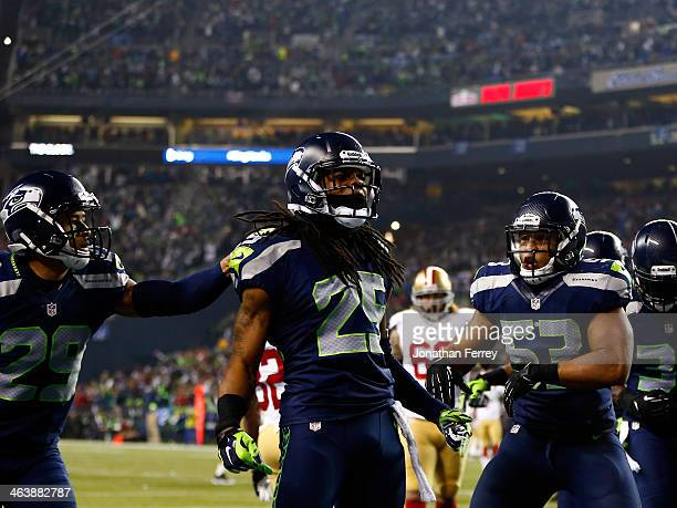 Cornerback Richard Sherman of the Seattle Seahawks celebrates after he tips the ball leading to an intereption by outside linebacker Malcolm Smith to...