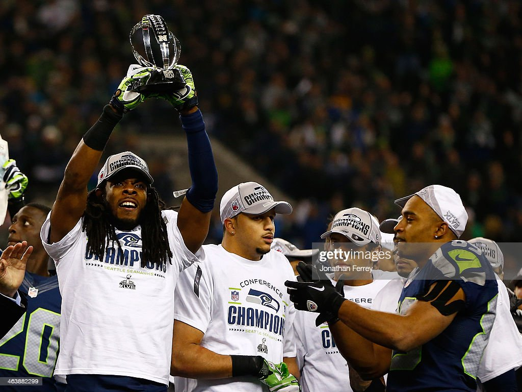 Cornerback Richard Sherman #25 of the Seattle Seahawks celebrates with the George Halas Trophy after the Seahawks defeat the San Francisco 49ers 23-17 in the 2014 NFC Championship at CenturyLink Field on January 19, 2014 in Seattle, Washington.