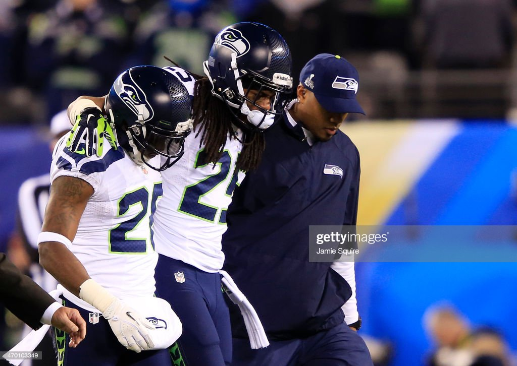 Cornerback Richard Sherman #25 of the Seattle Seahawks is helped off the field during the fourth quarter of Super Bowl XLVIII against the Denver Broncos at MetLife Stadium on February 2, 2014 in East Rutherford, New Jersey.