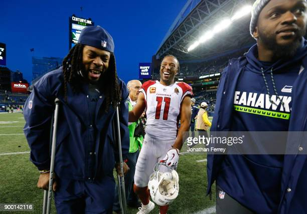 Cornerback Richard Sherman of the Seattle Seahawks laughs with wide receiver Larry Fitzgerald of the Arizona Cardinals and Cliff Avril after the game...