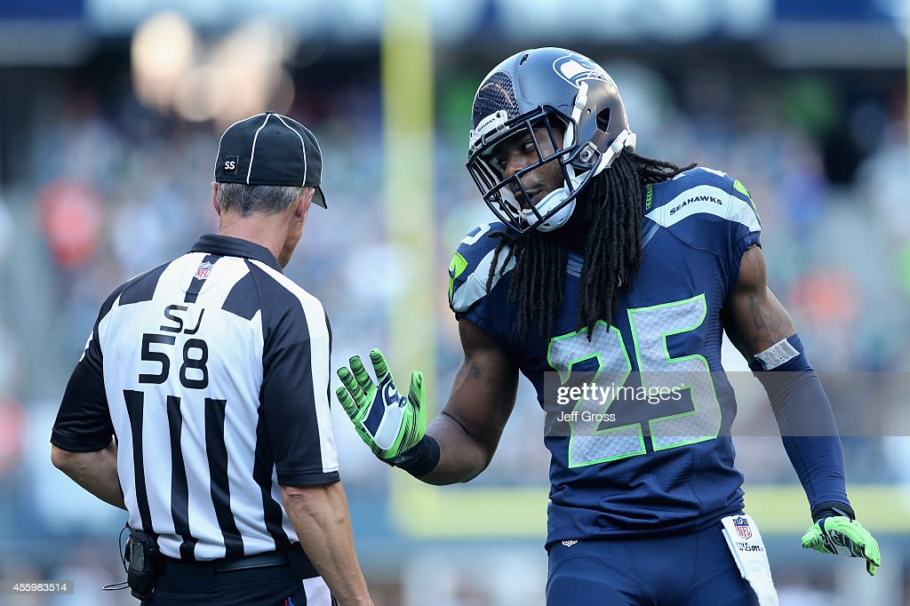 Cornerback Richard Sherman #25 of the Seattle Seahawks talks with side judge Jimmy DeBell #58 against the Denver Broncos at CenturyLink Field on September 21, 2014 in Seattle, Washington.