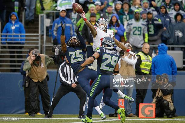 Cornerback Richard Sherman of the Seattle Seahawks tips a pass intended for wide receiver Odell Beckham Jr #13 of the New York Giants at CenturyLink...