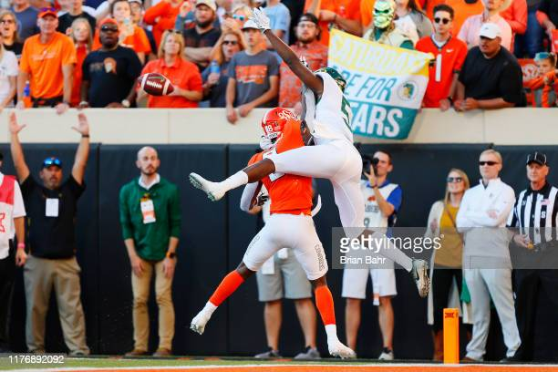 Cornerback Rodarius Williams of the Oklahoma State Cowboys plows into wide receiver Denzel Mims of the Baylor University Bears for a pass...