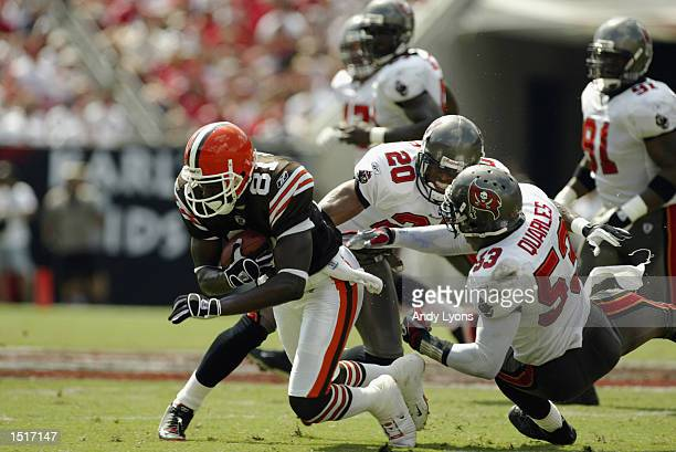 Cornerback Ronde Barber and linebacker Shelton Quarles of the Tampa Bay Buccaneers tackle wide receiver Quincy Morgan of the Cleveland Browns during...