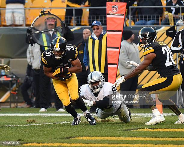 Cornerback Ross Cockrell of the Pittsburgh Steelers intercepts a pass intended for tight end Clive Walford of the Oakland Raiders as safety Will...