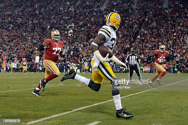 Cornerback Sam Shields of the Green Bay Packers runs the ball back for touchdown after an interception against quarterback Colin Kaepernick of the...