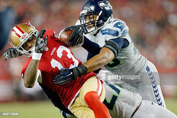 Cornerback Tharold Simon and linebacker KJ Wright of the Seattle Seahawks tackle wide receiver Stevie Johnson of the San Francisco 49ers on an...