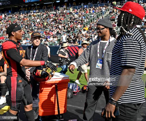 Cornerback Treston Decoud of the Dallas Renegades shakes hands with Todd Gurley of the Los Angeles Rams as Melvin Gordon of the Los Angeles Chargers...