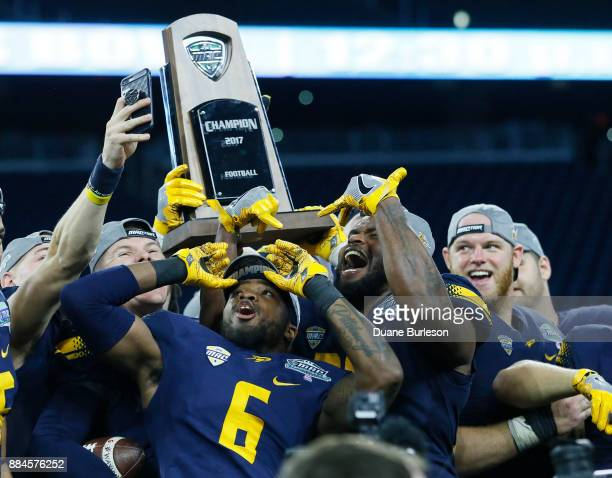 Cornerback Trevon Mathis of the Toledo Rockets and linebacker Ja'Wuan Woodley of the Toledo Rockets celebrate with teammates and the MAC Championship...