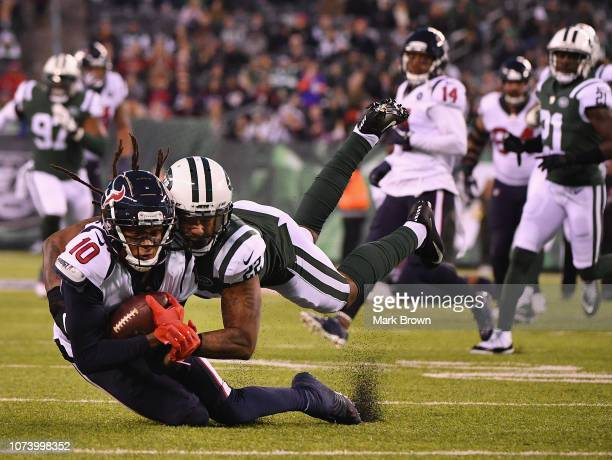 Cornerback Trumaine Johnson of the New York Jets tackles wide receiver DeAndre Hopkins of the Houston Texans at MetLife Stadium on December 15 2018...