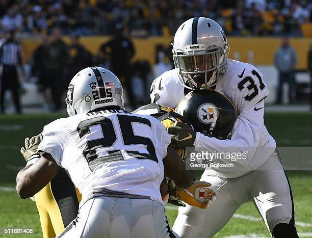 Cornerbacks Neiko Thorpe and DJ Hayden the Oakland Raiders tackle wide receiver Antonio Brown of the Pittsburgh Steelers at Heinz Field on November...