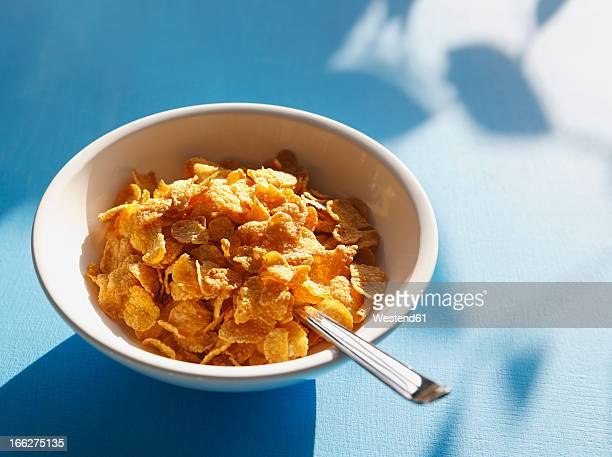 Cornflakes and spoon in bowl, close-up