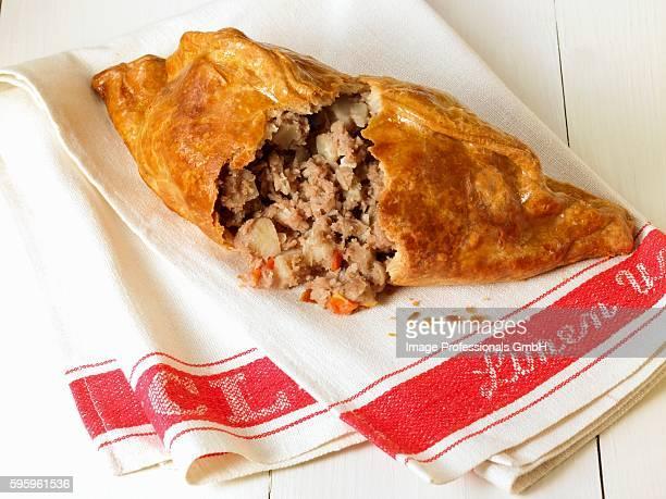 cornish pasty, broken open on a tea towel - cornish pasty stock-fotos und bilder