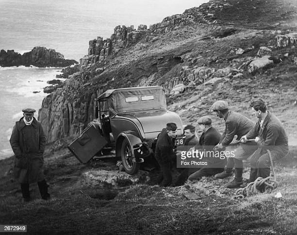 Cornishmen haul a softtop Morris tourer car up a cliff at Lands End after high speed winds blew it off the road