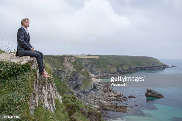 uk, cornwall, gwithian, businessman sitting at the coast looking at view - グイチアン ストックフォトと画像