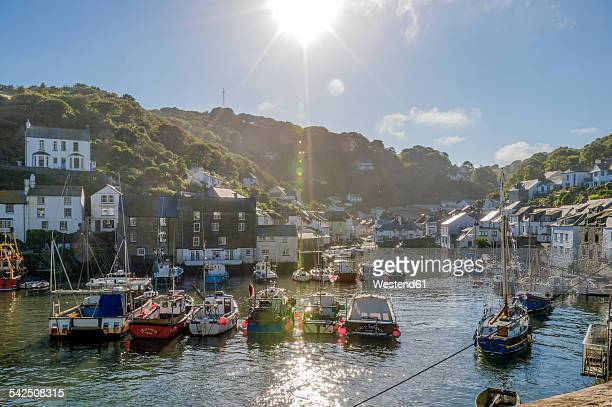 uk, cornwall, polperro, fishing boats in harbor in back light - fishing village stock pictures, royalty-free photos & images