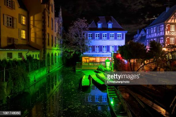 Corofully illuminated canal and building facade at Petite Venice quarter of Colmar town at night.