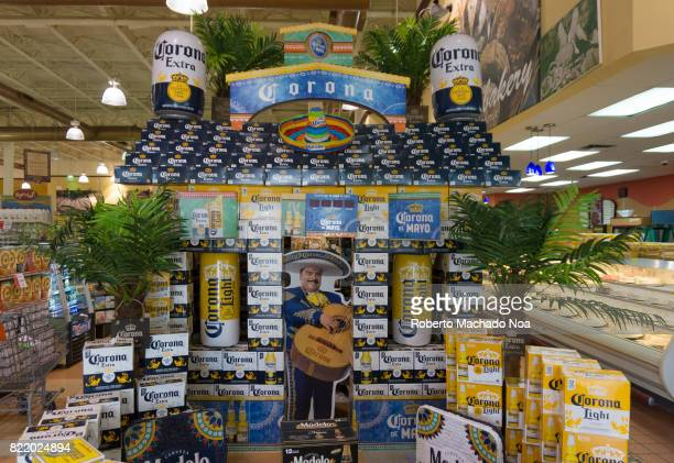 Corona beer display at the entrance of grocery store Floor to ceiling display with giant cans and palm plants in a shopping store