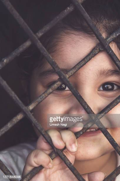 covid-19 corona virus concept, little girl in medical mask looking through window at home. smiling kid during quarantine due to covid. - lockdown stock pictures, royalty-free photos & images