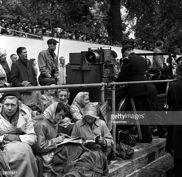 1953 Coronation of Queen Elizabeth II Coronation Procession London England Part of the crowd awaiting the procession warmly dressed and with books...