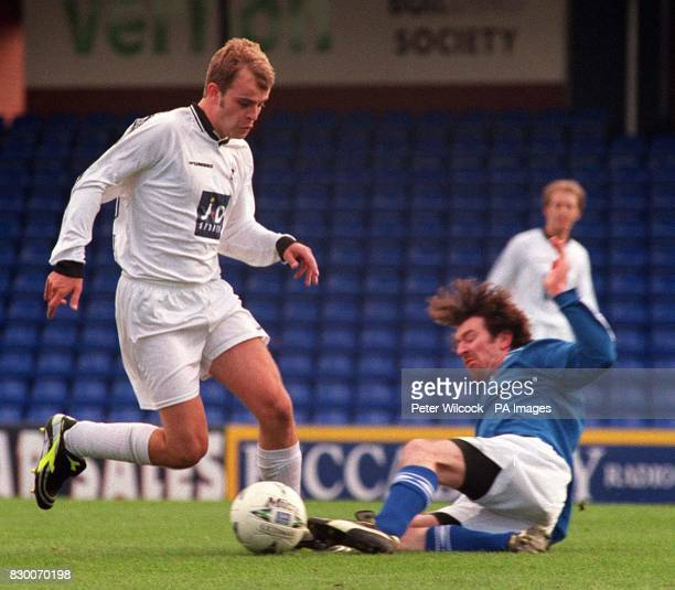 Coronation Street actor Simon Gregson is tackled by Eastenders' Sean Gleason during a charity football match at Stockport County FC between the cast...