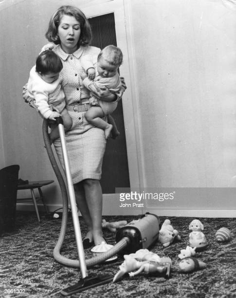 Coronation Street actress Anne Reid seen here doing the hoovering holding her screen twins Susan and Peter under her arms.