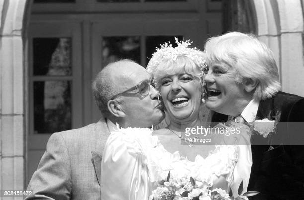 Coronation Street barmaid Bet Lynch gets a kiss from television groom Alec Gilroy and best man Charles Halliday after the TV wedding at the Holy...