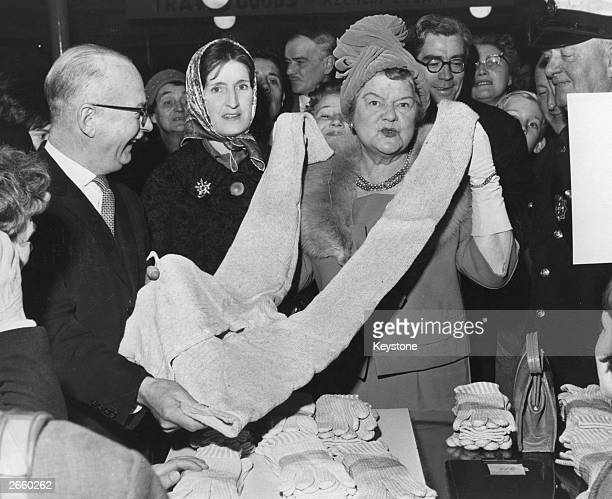 Coronation Street's Ena Sharples alias actress Violet Carson inspecting a pair of woollen combinations in the bargain basement of Painting's Store