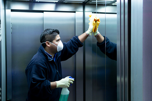 coronavirus. cleaning staff disinfecting elevator to avoid contagion 1216383997