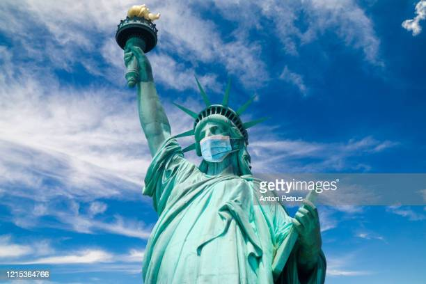 coronavirus covid-19 in usa. statue of liberty in a medical mask - corona landmarks stock pictures, royalty-free photos & images
