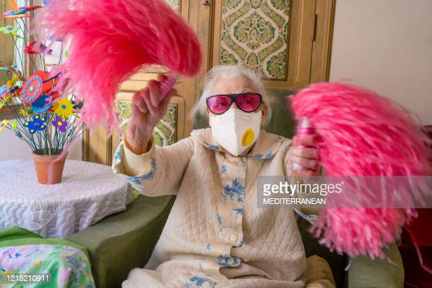 coronavirus covid-19 pandemic confinement with mask an humor cheerleader pom-pom elderly woman happy - funny surgical mask stock pictures, royalty-free photos & images
