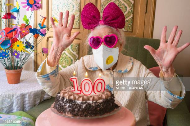 coronavirus covid-19 pandemic confinement with mask in 100 years old birthday cake old woman humor - confined space stock pictures, royalty-free photos & images