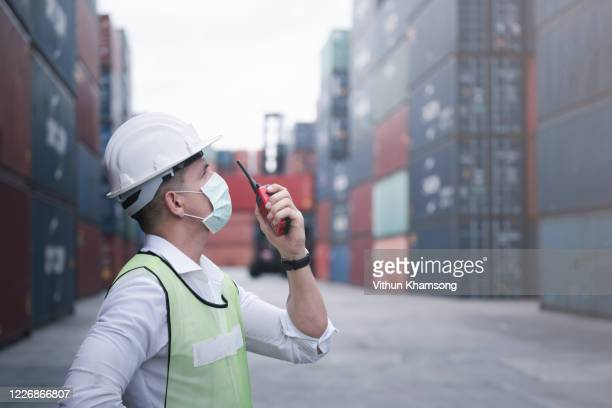coronavirus disease or covid can spread easily without mask. quarantined masked workers protect spreading of covid 19 by wearing face masks. workers are engineer wear masks during quarantine time - prevention photos et images de collection