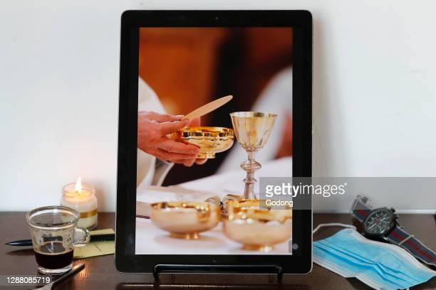 Coronavirus epidemic . Catholic mass on smartphone. Eucharist celebration. France.