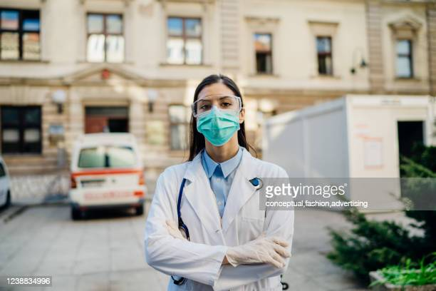 coronavirus infectologist in front of isolation hospital facility.coronavirus covid-19 expert.medical professional with protective glasses and mask prepared for virus outbreak.brave doctor - coronavirus doctor stock pictures, royalty-free photos & images