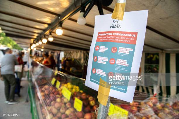 A coronavirus information leaflet sits beside cellophane barriers on a fruit and vegetable stall at Marche SaxeBreteuil in Paris France on Thursday...