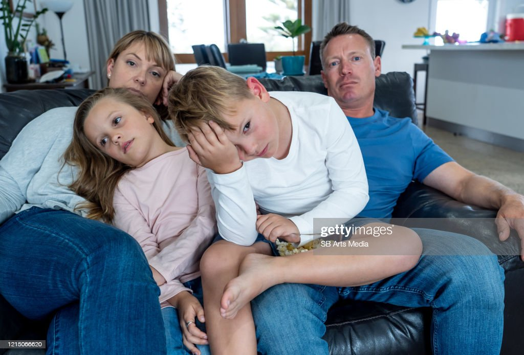 Coronavirus lockdow. Bored family watching tv helpless in isolation at home during quarantine COVID 19 Outbreak. Mandatory lockdowns and self isolation recommendations forces families stay home. : Stock Photo