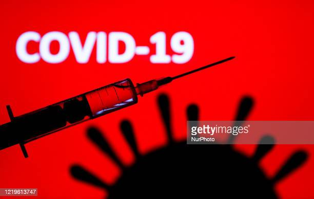 Coronavirus model and medical syringe are seen with 'covid19' sign displayed on a screen in the background in this illustration photo taken in Poland...
