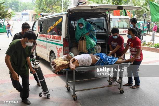 Coronavirus patient on a stretcher seen being taken to Mugda Medical College Hospital with his family members for treatment. Bangladesh extends...