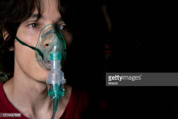 coronavirus patient wearing a nebuliser face mask - medical oxygen equipment stock pictures, royalty-free photos & images