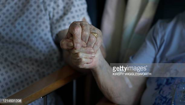 Coronavirus patients George Gilbert and his wife Domneva Gilbert 84, hold hands during a short visit as they are being treated in different areas and...