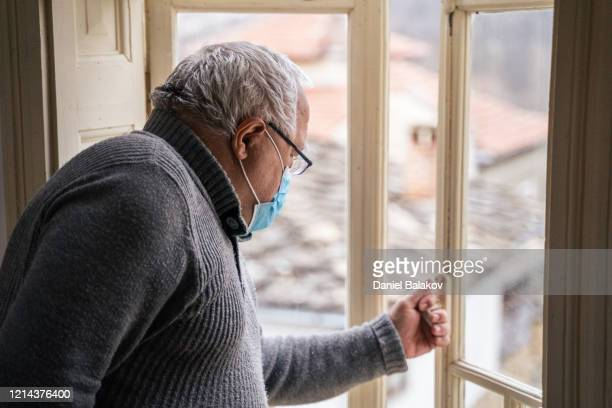 coronavirus protection. active senior man looking through window. wearing mask to avoid infectious diseases while at his home. - restraining stock pictures, royalty-free photos & images
