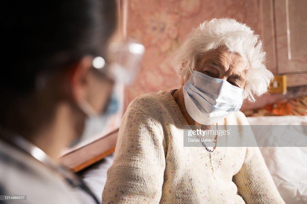 Coronavirus protection. Female doctor home visit during the quarantine. : Stock Photo