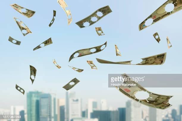 coronavirus punctured banknote flying in the sky - japan economy stock pictures, royalty-free photos & images