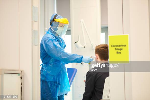 coronavirus screening at medical centre - protective suit stock pictures, royalty-free photos & images