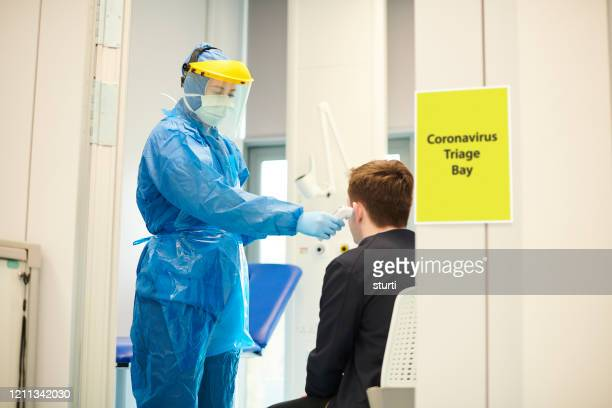 coronavirus screening at medical centre - protective workwear stock pictures, royalty-free photos & images