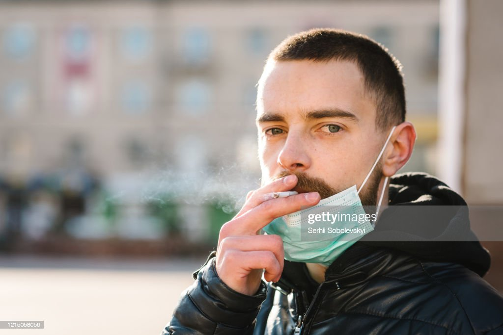 Coronavirus. Smoking. Closeup man with mask during COVID-19 pandemic smoking a cigarette at the street. Smoking causes lung cancer and other diseases. The dangers and harm of smoking. : Stock Photo